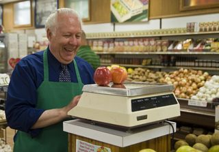 "Produce clerk David Neely laughs while weighing a customer's apples Monday at Ideal Grocery, 905 S. 27th St. ""The atmosphere is more relaxed"" than at bigger supermarkets, he said. ""You're able to develop a rapport with customers."" Photo by Hilary Stohs-Krause"
